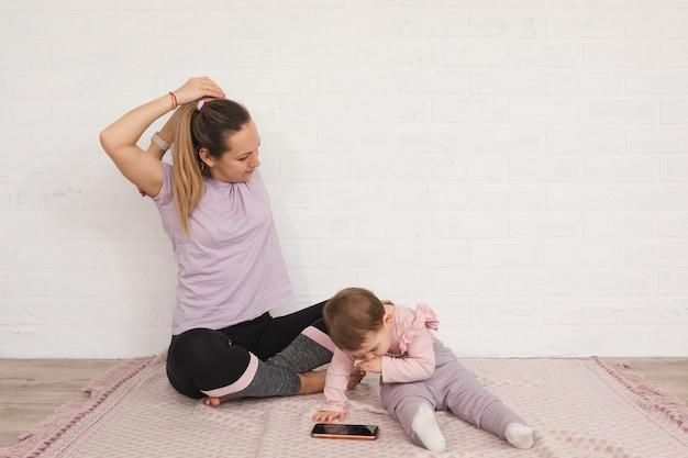 Młoda matka wykonuje ćwiczenia sportowe w domu, a jej roczna córka używa koncepcji macierzyństwa wielofunkcyjnego smartfona