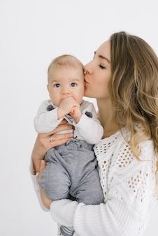 Młoda matka z blond włosami całuje swojego młodego syna i trzyma go w ramionach na białym tle