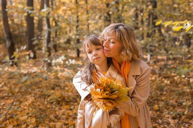 Młoda matka z córeczką w jesiennej koncepcji rodzicielstwa i dzieci w jesiennym parku
