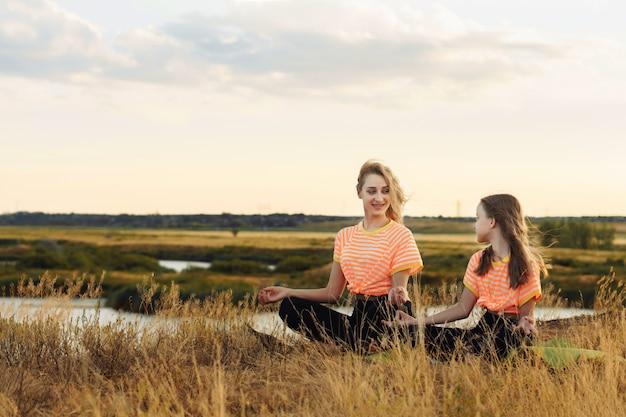 Młoda matka z córką w tych samych ubraniach co joga na świeżym powietrzu