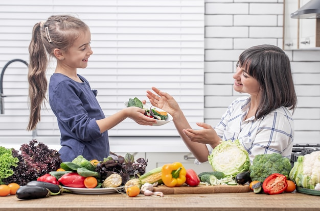 Młoda matka z córką z wieloma warzywami we wnętrzu nowoczesnej kuchni światła.