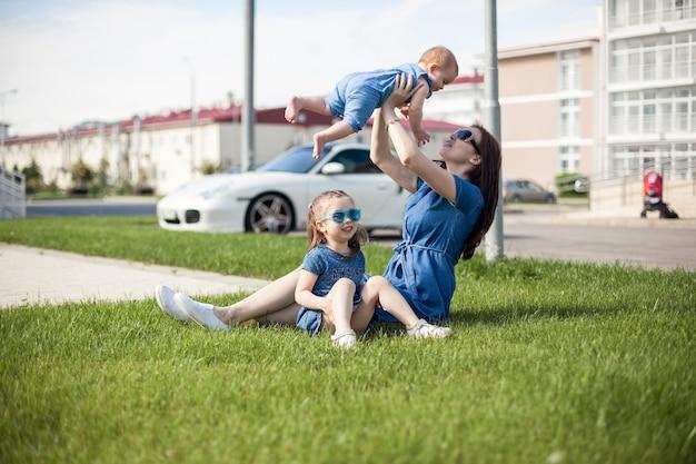 Młoda matka z córkami siedzi na trawie.