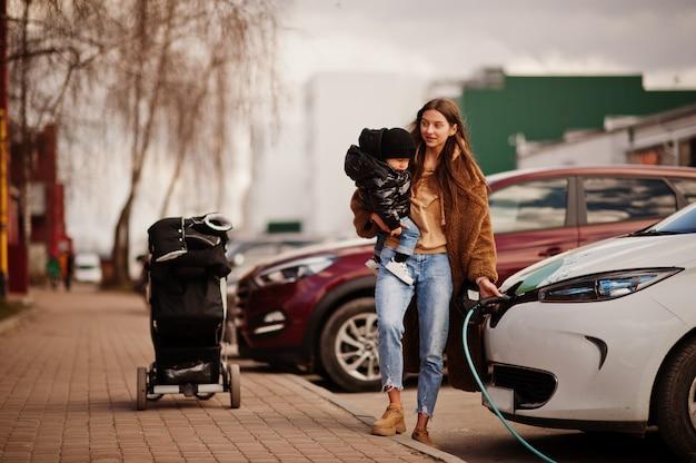 Młoda matka z dzieckiem ładowania samochodu elektrycznego na stacji benzynowej.