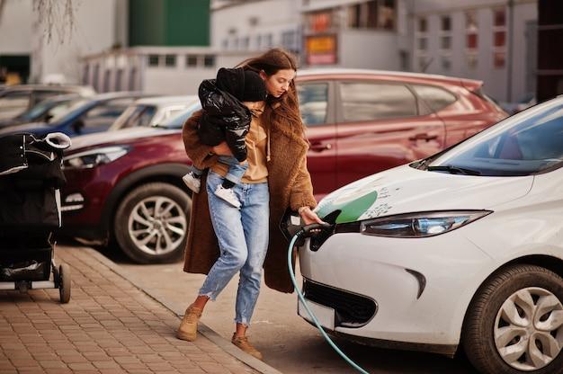 Młoda matka z dzieckiem ładowanie samochodu electro na elektrycznej stacji benzynowej.