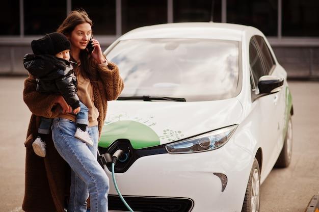 Młoda matka z dzieckiem ładuje samochód elektryczny na elektrycznej stacji benzynowej i mówi na telefon komórkowy.