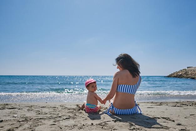 Młoda matka z dzieckiem na brzegu morza
