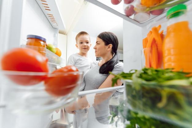 Młoda matka z dzieckiem w pobliżu otwartej lodówki. zdrowe odżywianie w domu koncepcja. warzywa i owoce w lodówce