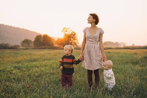 Młoda matka z dziećmi w słońcu o zachodzie słońca na przyrodzie na zewnątrz