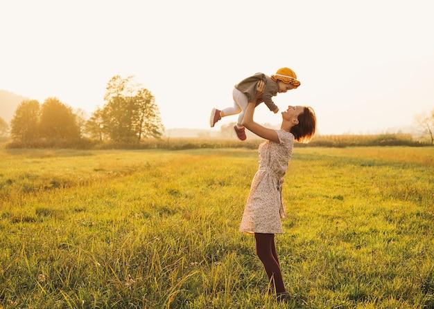 Młoda matka z dziećmi z balonami w słońcu o zachodzie słońca na przyrodzie na zewnątrz