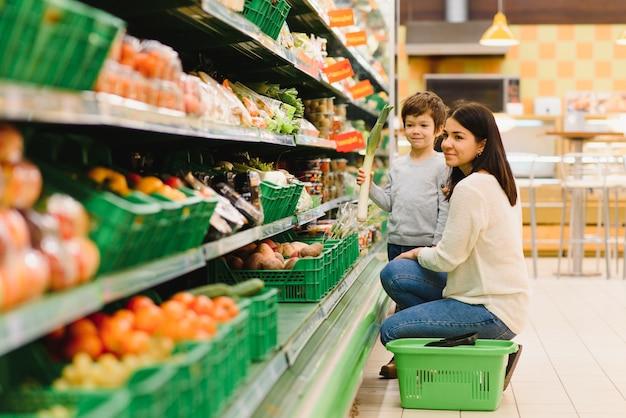 Młoda matka z jej małym chłopcem w supermarkecie