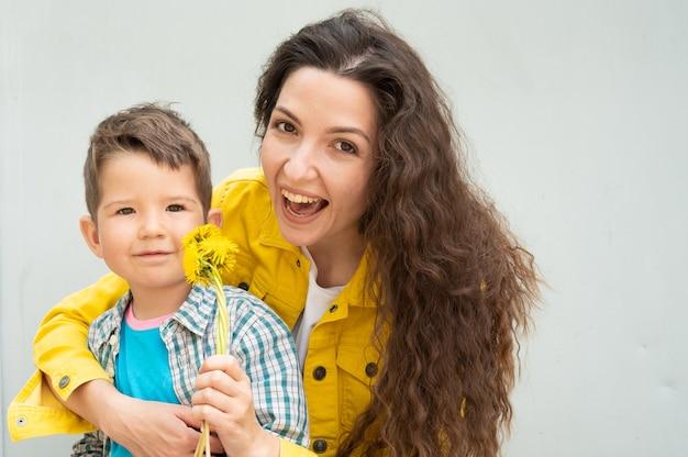 Młoda matka z kręconymi włosami i dzieckiem trzymającym kwiaty.