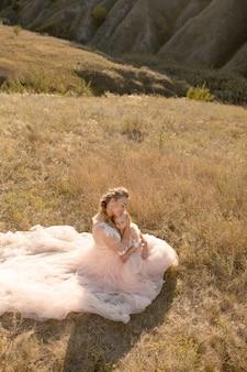 Młoda matka z małą córeczką w różowych sukienkach siedzi w polu. mama przytula córkę, przytulając ją