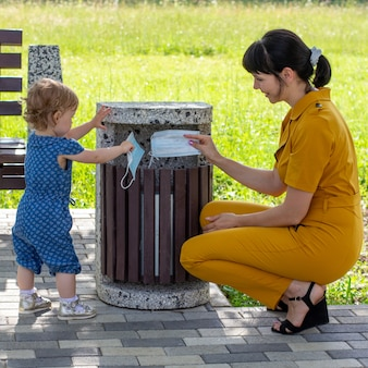 Młoda matka z małą córeczką wyrzuca maski medyczne do kosza w słoneczny letni dzień, koncepcja zakończenia pandemii koronawirusa