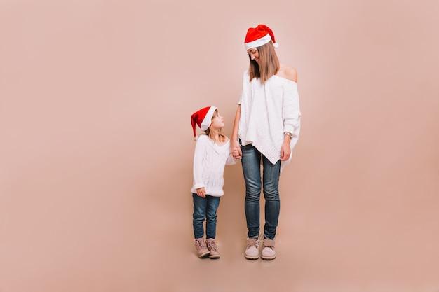 Młoda matka z małą ładną córeczką stojącą na beżowej ścianie w białych swetrach i czapkach mikołaja, patrząc na siebie i trzymając się za ręce