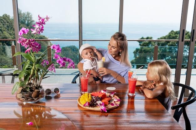 Młoda matka z synem i córką bawią się śniadanie w kuchni