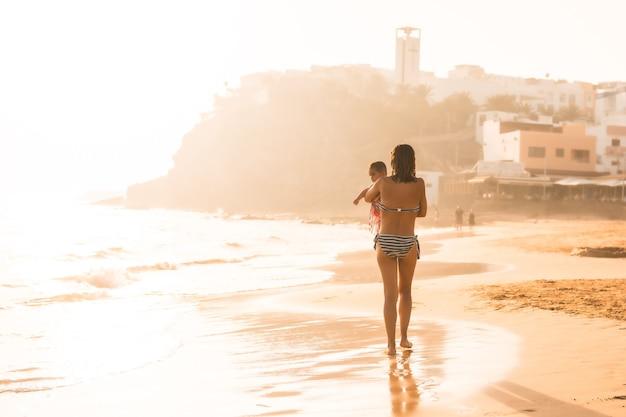 Młoda matka z sześciomiesięcznym dzieckiem o zachodzie słońca na plaży, morro jable, gmina pajara na południe od fuerteventury na wyspach kanaryjskich. hiszpania