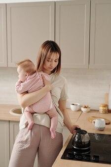 Młoda matka z uroczą córeczką stojącą przy kuchence elektrycznej