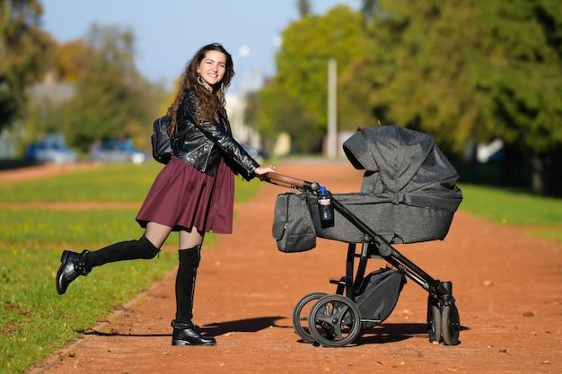 Młoda matka z wózkiem. koncepcja rodziny, dziecka i rodzicielstwa - szczęśliwa matka idzie z wózkiem w parku.