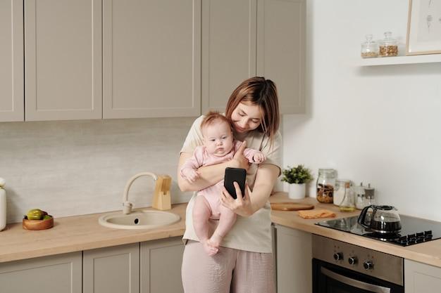 Młoda matka ze smartfonem trzymająca córeczkę