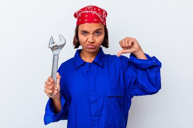 Młoda mechaniczna kobieta trzyma klucz na białym tle pokazując niechęć gest, kciuk w dół. pojęcie sporu.