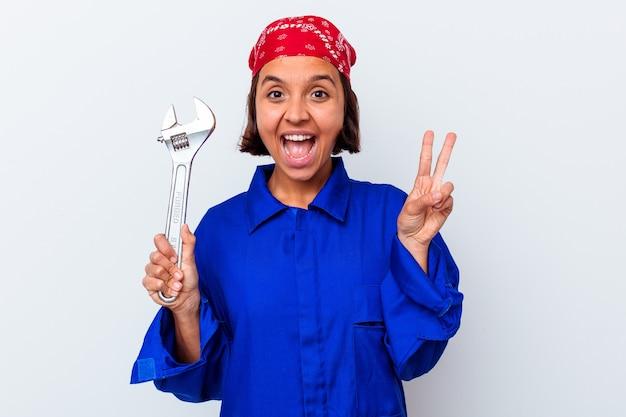 Młoda mechaniczna kobieta trzyma klucz na białym tle pokazując numer dwa palcami.