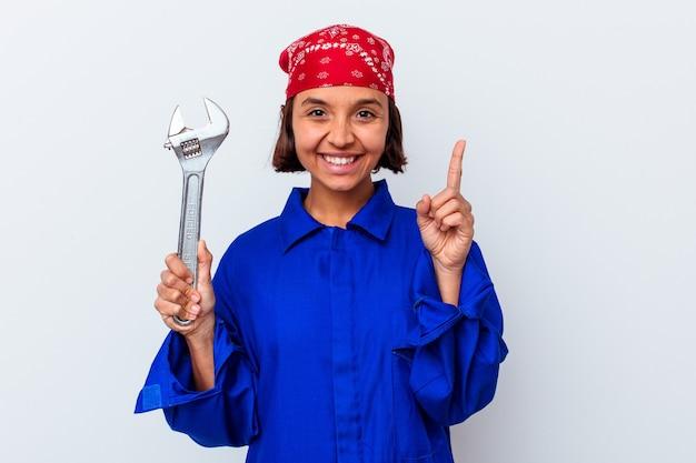 Młoda mechaniczna kobieta trzyma klucz na białym tle pokazując numer jeden z palcem.