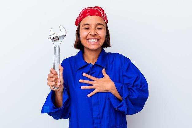 Młoda mechaniczna kobieta trzyma klucz na białym tle śmieje się głośno, trzymając rękę na klatce piersiowej.