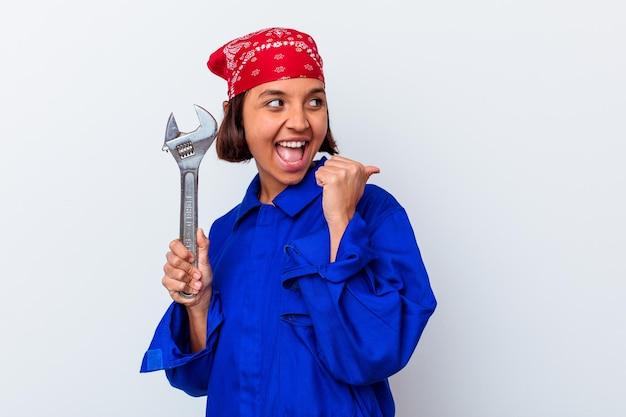 Młoda mechaniczna kobieta trzyma klucz odizolowane punkty z dala od kciuka, śmiejąc się i beztrosko.