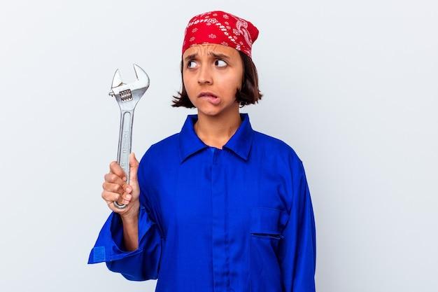 Młoda mechaniczna kobieta trzymająca klucz odizolowana, zdezorientowana, niepewna i niepewna.