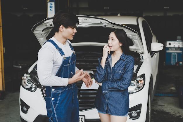 Młoda mechanika rozmowa o remontowym samochodzie kobieta lub właściciel przy samochodu sklepem