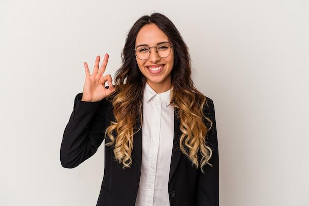 Młoda meksykańska biznesowa kobieta na białym tle mruga okiem i trzyma w porządku gest ręką.