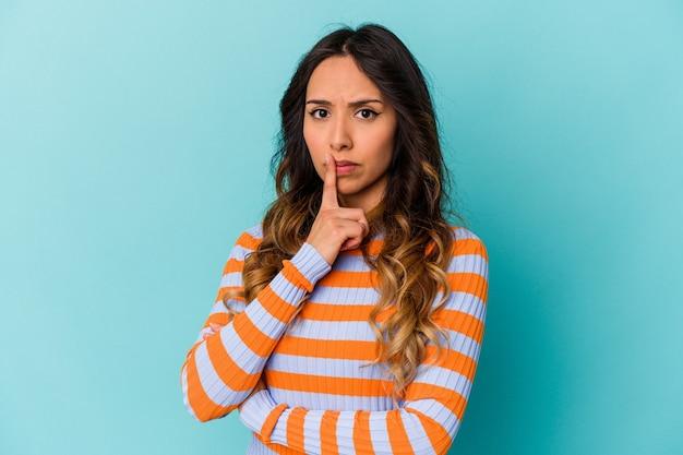 Młoda meksykańska kobieta na białym tle na niebieskiej ścianie niezadowolony patrząc w kamerę z sarkastycznym wyrazem.