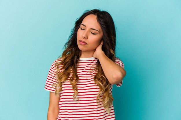 Młoda meksykańska kobieta na białym tle na niebieskiej ścianie o bólu szyi z powodu stresu, masowania i dotykania jej ręką.