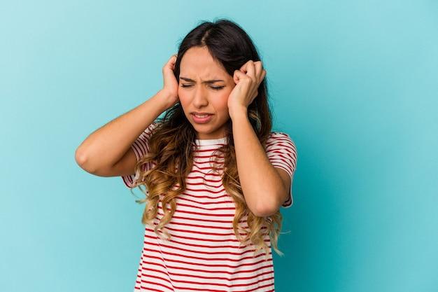 Młoda meksykańska kobieta na białym tle na niebieskiej ścianie obejmujące uszy rękami.