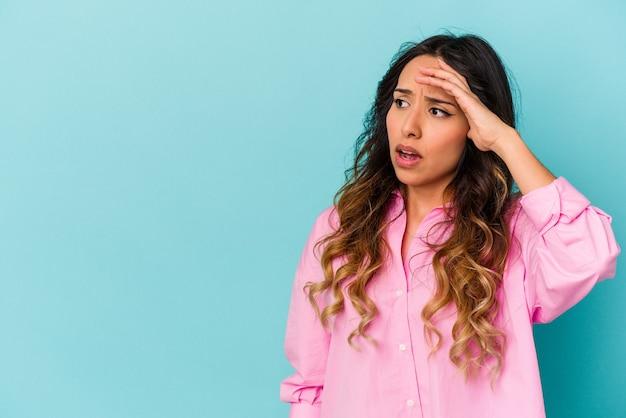 Młoda meksykańska kobieta na białym tle na niebieskiej ścianie, patrząc daleko, trzymając rękę na czole.
