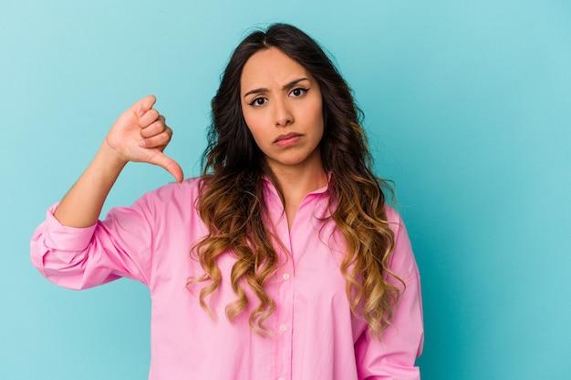 Młoda meksykańska kobieta na białym tle na niebieskiej ścianie, pokazując gest niechęci, kciuki w dół. pojęcie sporu.
