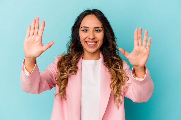 Młoda meksykańska kobieta na białym tle na niebieskiej ścianie pokazuje numer dziesięć rękami.