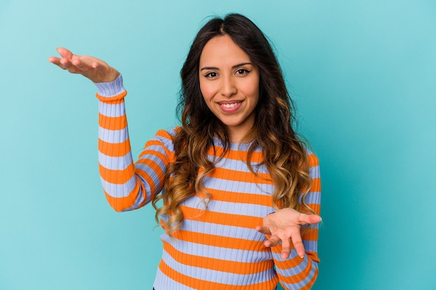 Młoda meksykańska kobieta na białym tle na niebieskiej ścianie robi skalę z rękami, czuje się szczęśliwa i pewna siebie.