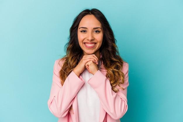 Młoda meksykańska kobieta na białym tle na niebieskiej ścianie trzyma ręce pod brodą, patrzy szczęśliwie na bok.