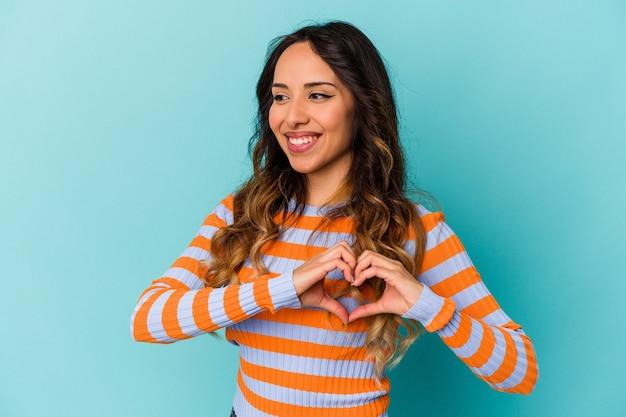 Młoda meksykańska kobieta na białym tle na niebieskiej ścianie, uśmiechając się i pokazując kształt serca rękami.