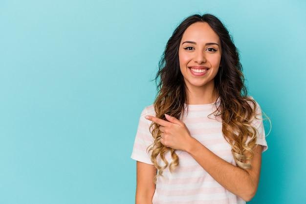 Młoda meksykańska kobieta na białym tle na niebieskiej ścianie, uśmiechając się i wskazując na bok, pokazując coś w pustej przestrzeni.