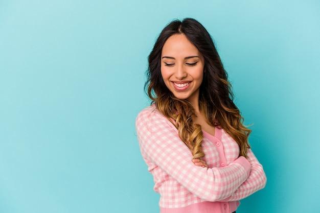 Młoda meksykańska kobieta na białym tle na niebieskiej ścianie, uśmiechając się pewnie ze skrzyżowanymi rękami.