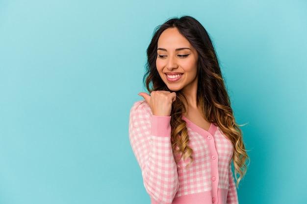 Młoda meksykańska kobieta na białym tle na niebieskiej ścianie wskazuje kciukiem z dala, śmiejąc się i beztrosko.