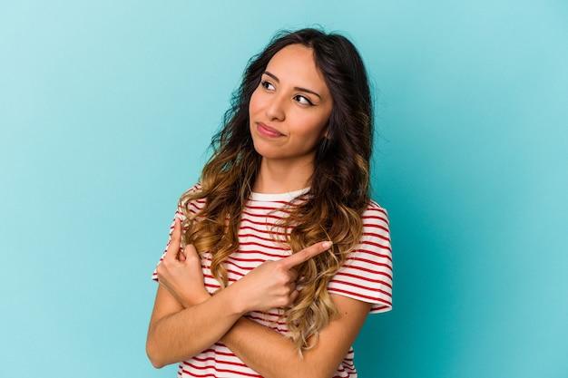 Młoda meksykańska kobieta na białym tle na niebieskiej ścianie wskazuje na boki, próbuje wybrać jedną z dwóch opcji.