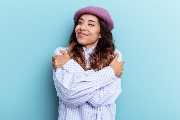 Młoda meksykańska kobieta na białym tle na niebieskim tle przytula się, uśmiechając się beztrosko i szczęśliwie.