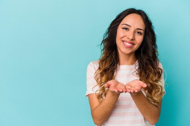 Młoda meksykańska kobieta na białym tle na niebieskim tle składane usta i trzymając dłonie, aby wysłać pocałunek powietrza.