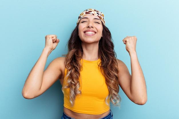 Młoda meksykańska kobieta na białym tle na niebieskim tle świętuje zwycięstwo, pasję i entuzjazm, szczęśliwy wyraz.