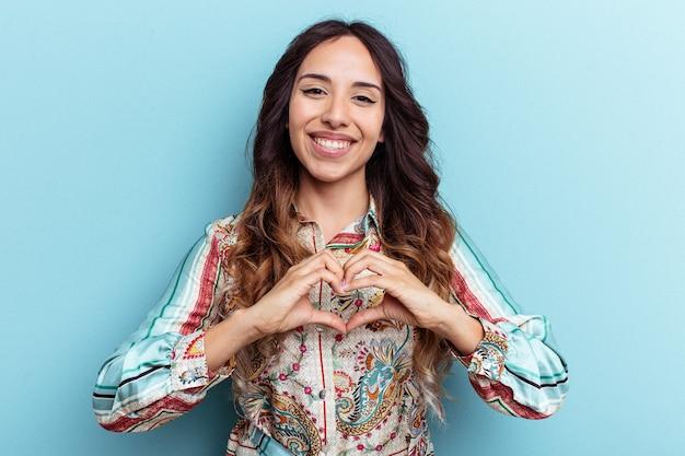 Młoda meksykańska kobieta na białym tle na niebieskim tle, uśmiechając się i pokazując kształt serca rękami.