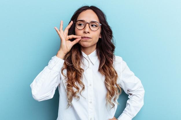 Młoda meksykańska kobieta na białym tle na niebieskim tle z palcami na ustach dochowując tajemnicy.