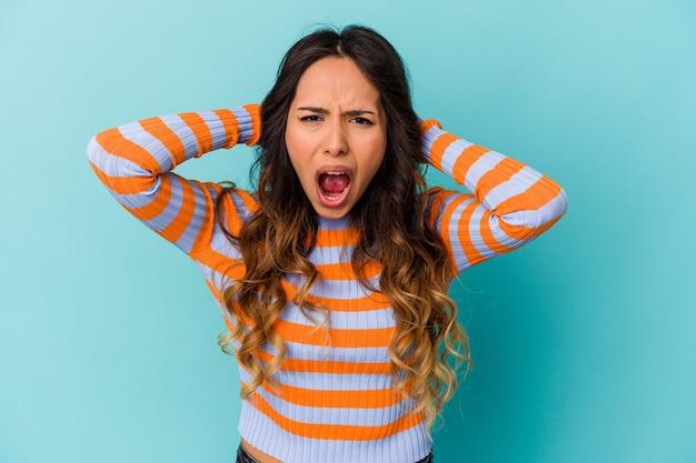 Młoda meksykańska kobieta na białym tle na niebiesko krzyczy z wściekłości.